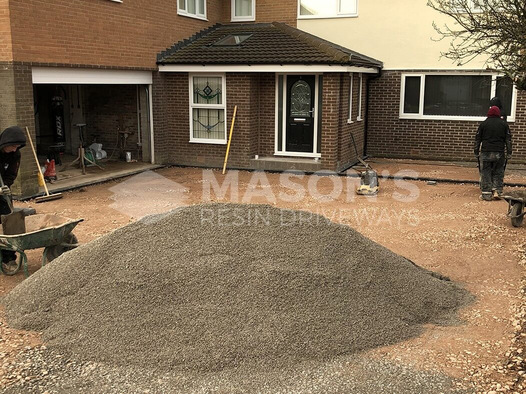 Worker on Leyland site completing block paving driveway