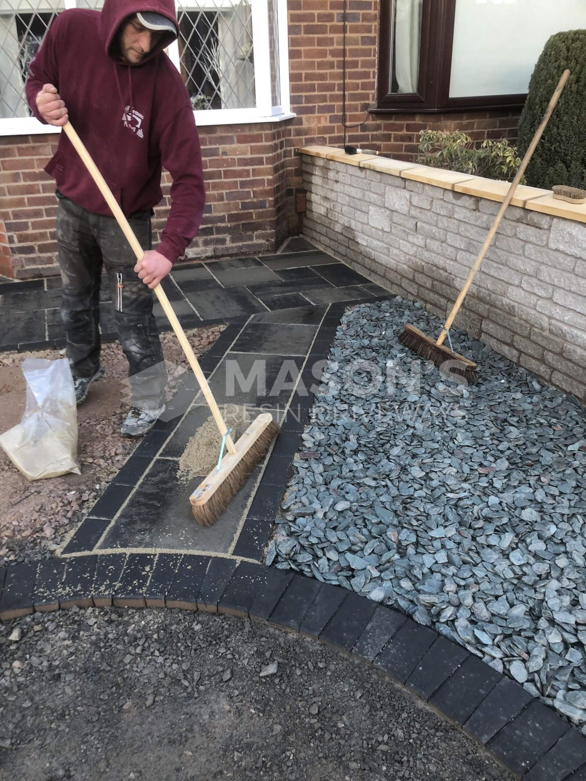 workers completing block paving on driveway in leyland near preston