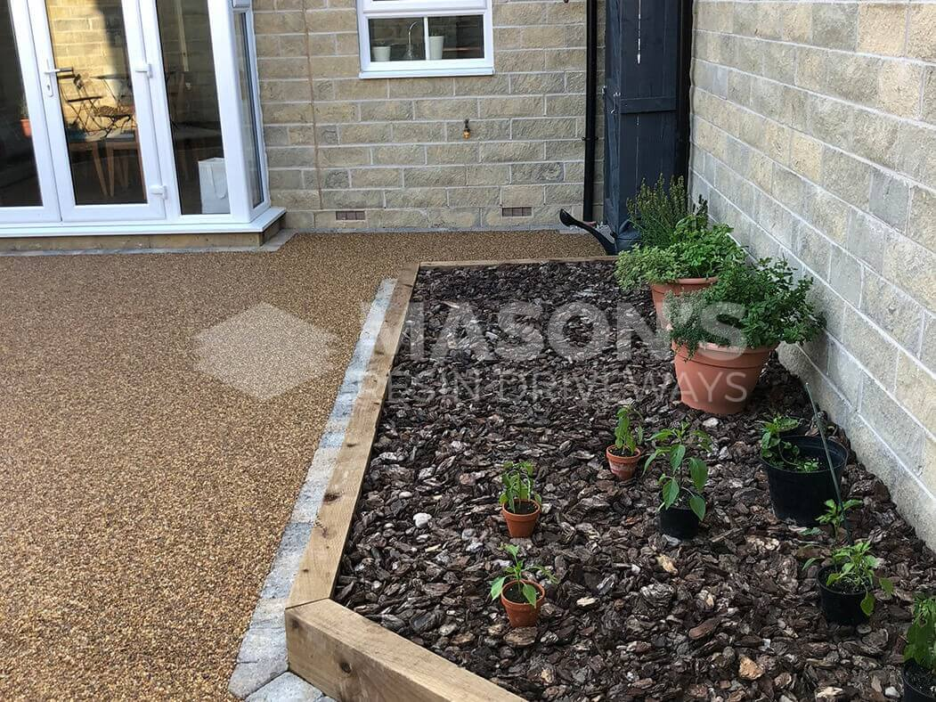 View of Resin Bound patio installed in Lancashire, near Preston with raised flower bed.