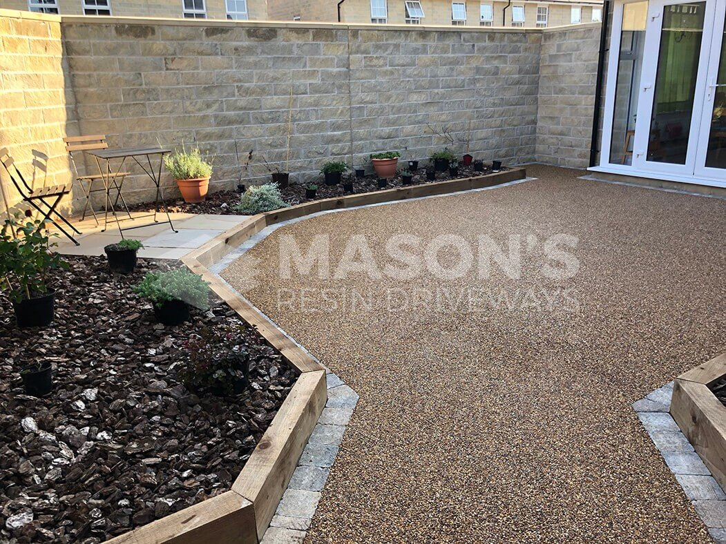 View of Resin Bound patio installed in Lancashire, near Preston showing raised flower beds and seating area.